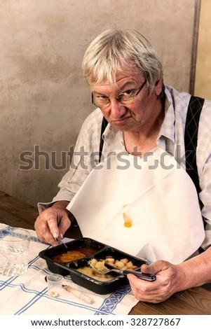 Elderly man in nursing home disliking his ready made dinner - stock photo