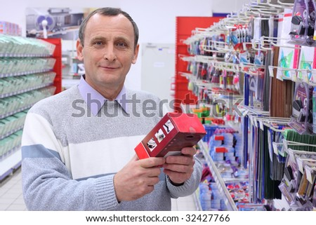 elderly man in shop with box in hands - stock photo