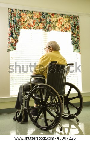 Elderly man in wheelchair sits and looks out of large window. Vertical shot. - stock photo