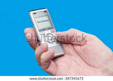 Elderly man is holding voice recorder on blue background, color and contrast manipulated - stock photo