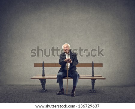 elderly man is sitting on a bench - stock photo