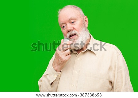 Elderly man is speaking to voice recorder on green background, color and contrast manipulated - stock photo