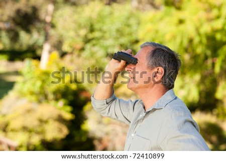 Elderly man looking at the sky with his binoculars - stock photo