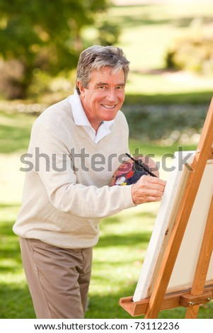 Elderly man painting in the park - stock photo