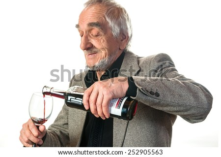 elderly man pours a glass of wine on a white - stock photo
