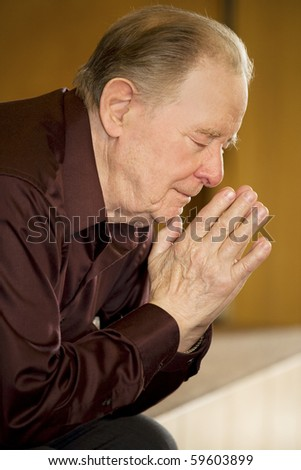 Elderly man praying in dark church - stock photo