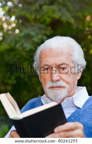 Elderly man reading a book outdoors, with green background. - stock photo