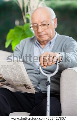 Elderly man reading newspaper while holding metal cane on couch at nursing home porch - stock photo