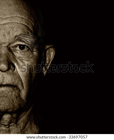 Elderly man's face over black background - stock photo