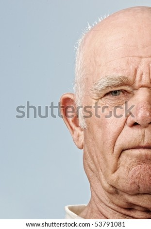 Elderly man's face over blue background - stock photo