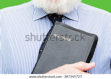 Elderly man, senior, is holding bible on chest background, color and contrast manipulated - stock photo
