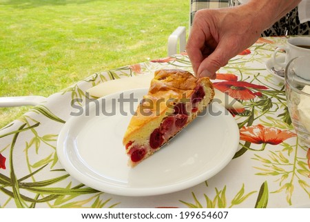 Elderly man serving a slice of juicy cherry cake on a garden table with cloth and coffee dishes - stock photo