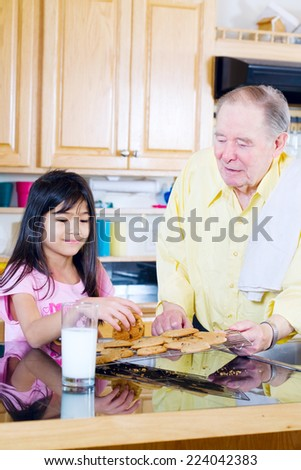 Elderly man sharing cookies with granddaughter - stock photo