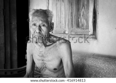 Elderly man sitting alone on the chair - stock photo