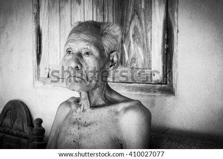 Elderly man sitting alone on the chair,black and white tone - stock photo