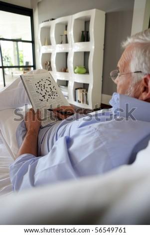 Elderly man sitting in a sofa doing crosswords - stock photo