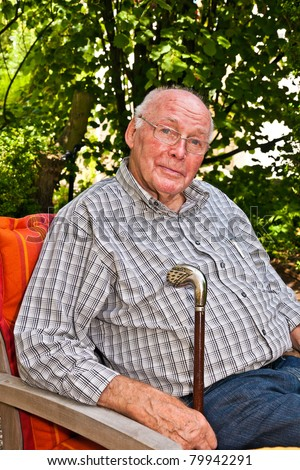 elderly man sitting in the garden in his armchair and enjoys life, concept happiness in age - stock photo
