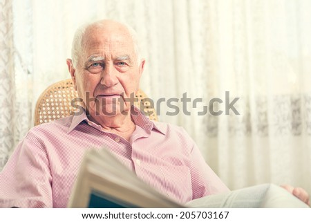 Elderly man sitting on chair reading newspaper at home - stock photo