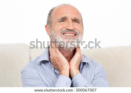 Elderly man sitting suffering from throat problems - stock photo