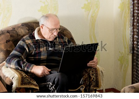 Elderly man sitting working on his laptop in a comfortable armchair at home - stock photo