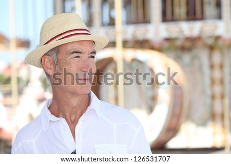 Elderly man standing in front of a carousel - stock photo