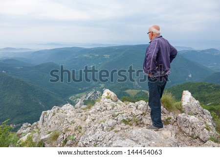 Elderly man standing on the edge of a cliff - stock photo