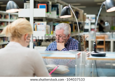 Elderly man studying among young college students in library and taking notes - stock photo