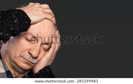 Elderly man suffering from a headache and toothache on gray background with copy-space - stock photo