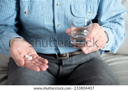 Elderly man taking medicament and holding glass of water - stock photo