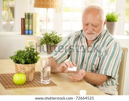 Elderly man taking pill at home, sitting at living room table.? - stock photo