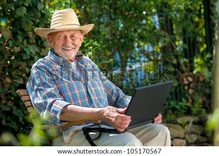 Elderly man using laptop in the park - stock photo