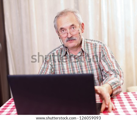 Elderly man using the laptop at home with a serious facial expression. - stock photo