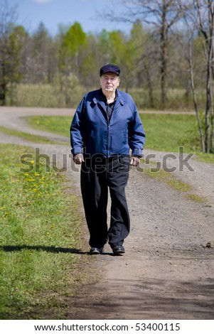 Elderly man walking on country road - stock photo