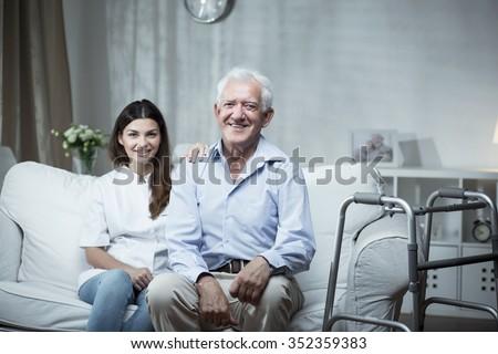 Elderly man with a community nurse visiting him - stock photo