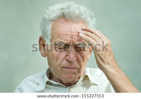 Elderly man with hand on his temple has a headache - stock photo