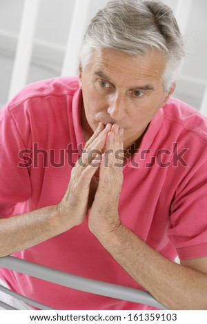 Elderly man with hands near his face looking down thinking- anxious face - stock photo