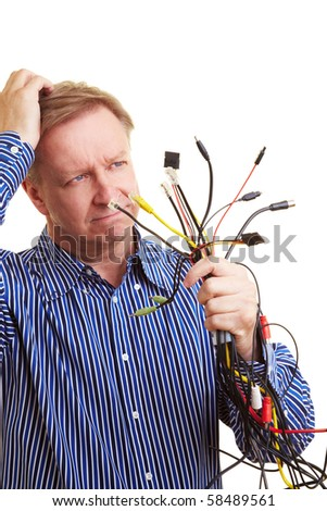Elderly man with many different cables in his hand looking perplexed - stock photo