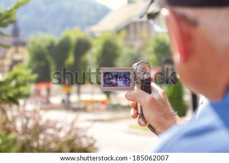 elderly man with video camera. focus on video camera - stock photo