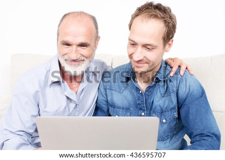 Elderly man with younger son looking on screen - stock photo