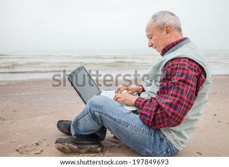 Elderly man working on a computer while sitting on the beach on a foggy day - stock photo