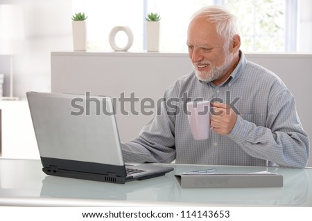 Elderly man working on laptop, smiling, looking at screen, drinking tea. - stock photo