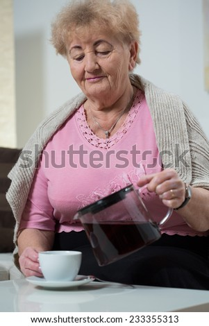 Elderly nice woman pouring the coffee to porcealin cup - stock photo