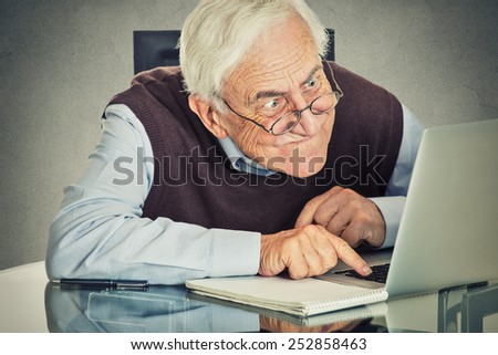 Elderly old man using computer sitting at table isolated on grey wall background. Senior people and technology concept  - stock photo