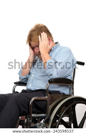Elderly paraplegic in wheelchair holds his head in his hands as he suffers from depression because of a medical problem. - stock photo