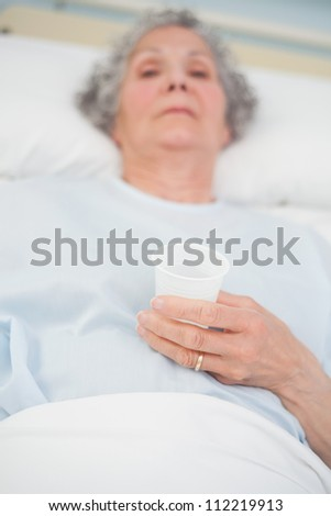 Elderly patient holding a plastic glass in her hand in hospital ward - stock photo