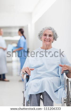 Elderly patient in a wheelchair in a corridor in hospital ward - stock photo