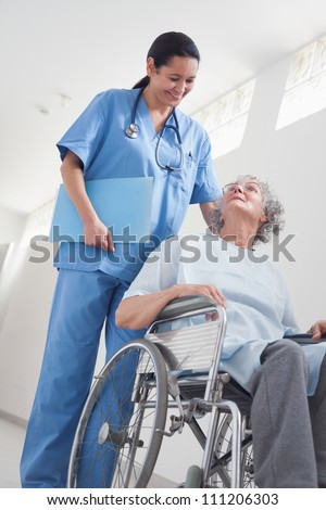 Elderly patient in a wheelchair next to a nurse in hospital ward - stock photo