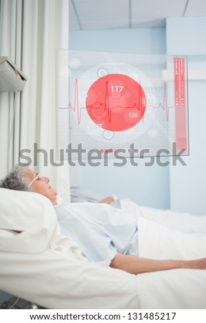 Elderly patient lying in hospital bed with futuristic ECG data display in a hospital ward - stock photo