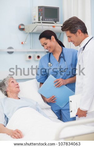 Elderly patient talking to a doctor and a nurse in hospital ward - stock photo