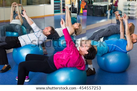 Elderly people stretching in a gym on fitness balls - stock photo